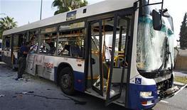 Израильский полицейский осматривает поврежденный в результате взрыва автобус в Тель-Авиве 21 ноября 2012 года. Взрыв произошел в среду в рейсовом автобусе в центре Тель-Авива, ранения получили десять человек, сообщила израильская служба скорой помощи. REUTERS/Nir Elias