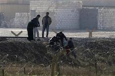Aviones de combate sirios bombardearon el miércoles un suburbio de Damasco, dijeron activistas de la oposición, mientras se intensifican los combates por segundo día consecutivo en las afueras de la ciudad, desafiando el control del presidente Bashar al Asad sobre la capital. En la imagen, refugiados sirios tratan de cruzar la frontera hacia Turquía en la ciudad siria de Ras al Ain, el 21 de noviembre de 2012. REUTERS/Amr Abdallah Dalsh