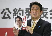 Presidente do Partido Liberal Democrático (PLD), de oposição, Shinzo Abe, mostra folheto da plataforma de campanha do partido para as eleições parlamentares em dezembro, em Tóquio, em foto da Kyodo. 21/11/2012 REUTERS/Kyodo