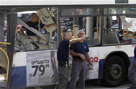 Israeli police officers stand next to a damaged bus at the scene of an explosion in Tel Aviv November 21, 2012. A bomb exploded on a bus in central Tel Aviv on Wednesday, wounding at least 10 people in what officials said was a terrorist attack that could complicate efforts to secure a ceasefire in the Gaza Strip. REUTERS/Nir Elias (ISRAEL - Tags: POLITICS CIVIL UNREST)