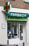 Las farmacias españolas amenazaron el miércoles con dejar de pagar impuestos y los suministros de sus proveedores ante la falta de una solución definitiva a sus problemas de financiación y de impagos de sus facturas por parte de las administraciones públicas. En la imagen, una mujer limpia un cristal de una farmacia en Madrid, el 18 de abril de 2012. REUTERS/Andrea Comas