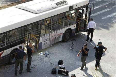 Israeli police explosives experts stand next to a damaged bus at the scene of an explosion in Tel Aviv November 21, 2012. A bomb exploded on a bus in central Tel Aviv on Wednesday, wounding at least 10 people in what officials said was a terrorist attack that could complicate efforts to secure a ceasefire in the Gaza Strip. REUTERS/Nir Elias
