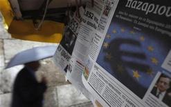 El ministro de Finanzas de Alemania, Wolfgang Schaeuble, dijo el miércoles que los gobiernos de la zona euro y el Fondo Monetario Internacional acordaron un programa de recompra de deuda griega entre una serie de medidas destinadas a cubrir las necesidades de financiación del país. En la imagen, un hombe pasa junto a un periódico con un logo del euro en su portada en el centro de Atenas, el 21 de noviembre de 2012. REUTERS/John Kolesidis