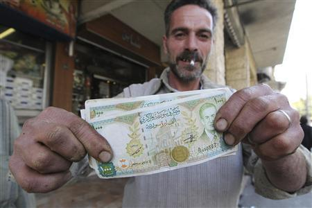 A vendor displays Syrian currency notes in Damascus November 13, 2012. Plunging public revenues are a sign of the fiscal pressures Damascus is facing in the wake of the 20-month uprising against President Bashar al-Assad's regime, which has crippled industrial output and oil production and triggered a sharp depreciation in the Syrian currency. Picture taken November 13, 2012. To match Feature SYRIA-ECONOMY/ REUTERS/Muzaffar Salman