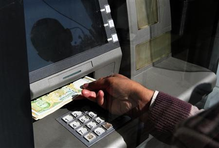 A man uses an ATM machine in this picture taken through a glass panel, in Damascus November 13, 2012. Plunging public revenues are a sign of the fiscal pressures Damascus is facing in the wake of the 20-month uprising against President Bashar al-Assad's regime, which has crippled industrial output and oil production and triggered a sharp depreciation in the Syrian currency. Picture taken November 13, 2012. To match Feature SYRIA-ECONOMY/ REUTERS/Muzaffar Salman