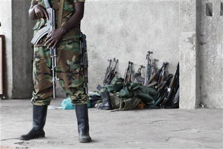 A M23 rebel guards weapons returned by the government's army in Goma city November 21, 2012. Rebel forces in eastern Congo said on Wednesday they planned to take control of the whole of the vast central African country after they captured the eastern town of Goma while United Nations peacekeepers looked on. REUTERS/James Akena