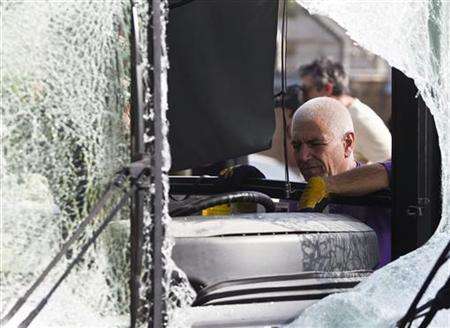 A bus company worker looks at a damaged bus before towing it from the scene of an explosion in Tel Aviv November 21, 2012. REUTERS/Baz Ratner (ISRAEL - Tags: CIVIL UNREST POLITICS TRANSPORT)