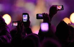"""Поклонники фотографируют на мобильные телефоны шоу телеканала VH1 """"Divas Salute The Troops"""" в Сан-Диего 3 декабря 2010 года. Производитель телекоммуникационного оборудования Ericsson ждет ежегодного удвоения объема передаваемых мобильными устройствами данных вплоть до 2018 года. REUTERS/K.C. Alfred"""