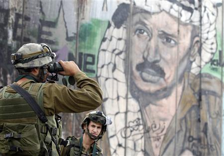 An Israeli soldier looks through binoculars in front of a mural depicting the late Palestinian leader Yasser Arafat on the controversial Israeli barrier, during clashes with Palestinian stone-throwers at Qalandiya checkpoint near the West Bank city of Ramallah November 21, 2012. Clashes broke out between Palestinians and the Israeli army in multiple locations across the occupied West Bank on Wednesday, underlining heightened tensions by the Gaza conflict. REUTERS/Marko Djurica