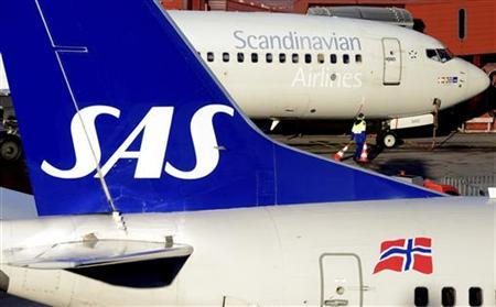 A ground staffer carries warning cones between two SAS Boeing 737 aircrafts parked at Arlanda airport's Terminal Five, north of Stockholm November 13, 2012. REUTERS/Johan Nilsson/Scanpix