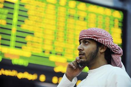An investor looks up at electronic boards displaying stock information at the ADX Abu Dhabi Securities Exchange stock market October 23, 2012. REUTERS/Ben Job