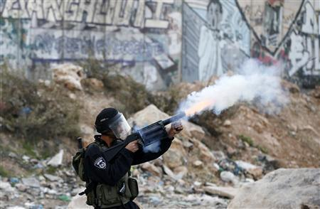 An Israeli border policeman fires tear gas canisters at Palestinian stone-throwers during minor clashes against Israel's military operation in the Gaza Strip in Qalandiya checkpoint near the West Bank city of Ramallah November 21, 2012. REUTERS/Marko Djurica