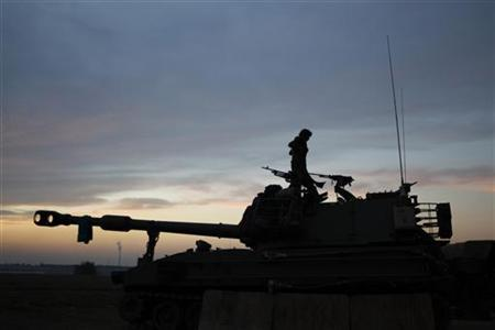 An Israeli soldier stands atop a mobile artillery unit positioned outside the northern Gaza Strip November 21, 2012. REUTERS/Darren Whiteside