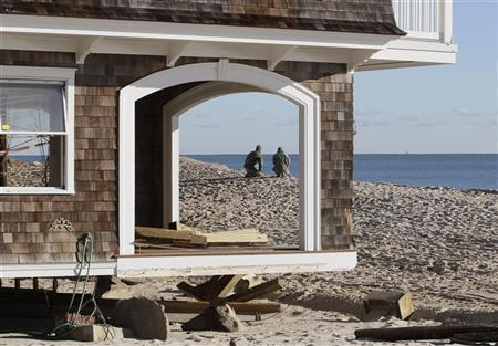 Two National Guardsmen, seen through empty window frames of a home, pause while on patrol at the beach front, to look at the ocean in the aftermath of Hurricane Sandy, at Bay Head, New Jersey November 4, 2012. REUTERS/Tom Mihalek