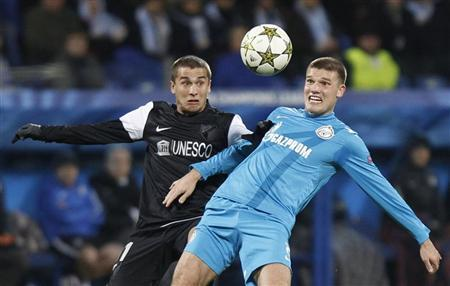 Zenit St. Petersburg's Igor Denisov (R) fights for the ball with Malaga's Seba during their Champions League Group C soccer match at the Petrovsky stadium in St. Petersburg November 21, 2012. REUTERS/Alexander Demianchuk