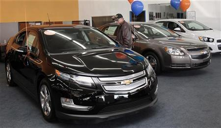 A potential customer looks at a black 2012 Chevrolet Volt electric vehicle in the showroom of George Matick Chevrolet auto sales in Redford, Michigan January 31, 2012. REUTERS/Rebecca Cook