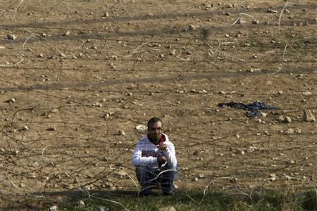 A Syrian man sits near a railway track as he looks across the border fence from the northern Syrian town of Ras al-Ain into Turkey, as seen from the Turkish border town of Ceylanpinar, Sanliurfa province, November 21, 2012. Turkey has asked NATO to deploy Patriot missiles on its territory, the alliance said on Wednesday, to help it defend itself against any Syrian attacks. Sporadic gunfire was heard throughout the day at the border. REUTERS/Amr Abdallah Dalsh