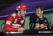 Red Bull Formula One driver Sebastian Vettel (R) of Germany offers his cap to Ferrari Formula One driver Fernando Alonso of Spain during a news conference following the Indian F1 Grand Prix at the Buddh International Circuit in Greater Noida, on the outskirts of New Delhi, October 28, 2012. REUTERS/Vijay Mathur