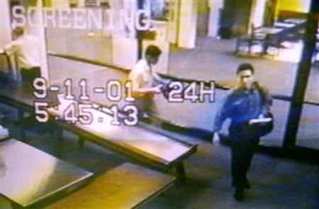 Two men identified by authorities as suspected hijackers Mohammed Atta (R) and Abdulaziz Alomari (C) pass through airport security September 11, 2001 at Portland International Jetport in Maine in an image from airport surveillance tape released September 19, 2001. REUTERS/PORTLAND POLICE DEPARTMENT-Handout HS/HB