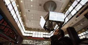 Um homem fala em telefone celular ao observar um display eletrônico na bolsa de valores BM&FBovespa em São Paulo. 4/8/2011 REUTERS/Nacho Doce