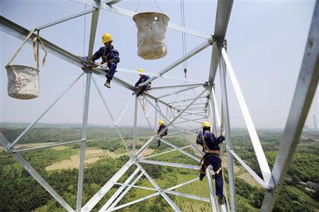 Workers install a high voltage electricity pylon in Xuancheng, Anhui province, in this May 17, 2011 file photo. REUTERS/Stringer/Files