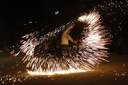 A Palestinian youth plays with firework as he celebrates what Palestinians say is a victory over Israel after an eight-day conflict in Gaza City November 21, 2012. Israel and the Islamist Hamas movement agreed on Wednesday to an Egyptian-sponsored ceasefire to halt an eight-day conflict around the Gaza Strip that has killed more than 140 Palestinians and five Israelis. REUTERS/Mohammed Salem