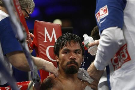 WBO welterweight champion Manny Pacquiao of the Philippines is treated in his corner between rounds during his title fight against Timothy Bradley Jr. of the U.S. at the MGM Grand Garden Arena in Las Vegas, Nevada June 9, 2012. REUTERS/Steve Marcus