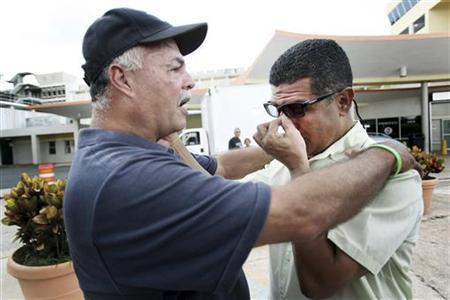Former boxer Lovi Callejas (R) and friend Ruben Borrali console each other as they await news on the condition of former Puerto Rican welterweight boxer Hector ''Macho'' Camacho outside the hospital, where Camacho is being treated for a gunshot wound to the face and neck, in San Juan November 21, 2012. REUTERS/Alvin Baez