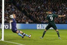 <p>Le Madrilène Karim Benzema trompe le gardien de Manchester City, Joe Hart. En tenant Manchester City en échec mercredi soir à l'Etihad Stadium (1-1), le Real Madrid a fait coup double: se qualifier pour les huitièmes de finale de la Ligue des champions et écarter de la course au titre un prétendant crédible. /Photo prise le 21 novembre 2012/REUTERS/Phil Noble</p>
