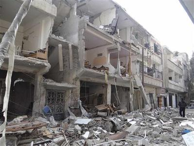 A man walks past buildings damaged after Syrian Air Force fighter jets loyal to Syria's President Bashar al-Assad fired missiles, in Erbeen, near Damascus November 20, 2012. REUTERS/Bassam al-Erbeeni/Shaam News Network/Handout