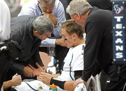 Jacksonville Jaguars quarterback Blaine Gabbert is examined on the bench after he was injured being sacked by Houston Texans safety Danieal Manning during their NFL football game in Houston November 18, 2012. REUTERS/Richard Carson