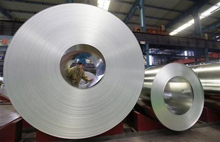 An employee checks on a steel product at a steel production factory in Wuhan, Hubei province, August 2, 2012. REUTERS/Stringer/Files