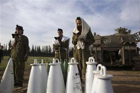 Israeli soldiers pray behind artillery shells near the border with the northern Gaza Strip November 21, 2012. REUTERS/Ronen Zvulun
