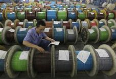 An employee inspects the newly-made optical cables at a factory in Wuhan, Hubei province July 25, 2012. REUTERS/Stringer
