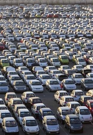 An employee walks among Chevrolet cars on yard at the General Motors plant in Asaka August 29, 2012. REUTERS/Shamil Zhumatov