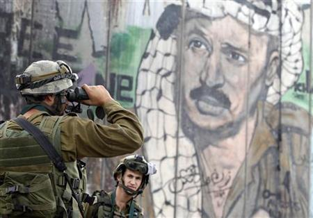 An Israeli soldier looks through binoculars in front of a mural depicting the late Palestinian leader Yasser Arafat on the controversial Israeli barrier, during clashes with Palestinian stone-throwers at Qalandiya checkpoint near the West Bank city of Ramallah November 21, 2012. REUTERS/Marko Djurica