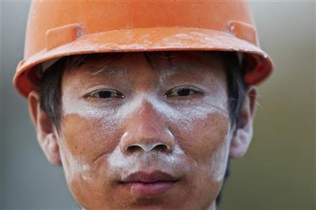 A migrant labourer poses for a photograph after finishing his work at a construction site in Shanghai November 13, 2012. REUTER/Aly Song