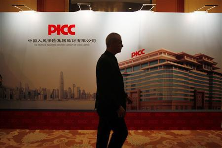 A man walks past a backdrop during an investors meeting of The People's Insurance Company (Group) of China Ltd (PICC) in Hong Kong November 22, 2012. REUTERS/Bobby Yip