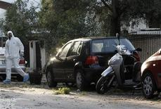 A Greek police explosives expert searches for evidence at the area outside a house in Chalandri suburb, north of Athens, November 22, 2012. REUTERS/John Kolesidis