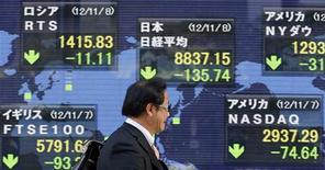 El Índice Nikkei subió un 1,6 por ciento a un máximo de 6-1/2 meses, reforzado por las ganancias producidas en los fabricantes de coches y de electrónica ante las expectativas de que un yen más flojo potencie sus resultados. En la imagen, un hombre pasa frente a un tablero electrónico que muestra los índices bursátiles, en Tokio, el 8 de noviembre de 2012. REUTERS/Yuriko Nakao