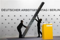 Berlino, operai finiscono di montare il palco al congresso annuale della Confindustria tedesca, lo scorso 16 ottobre. REUTERS/Thomas Peter