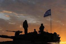 Soldati israeliani oggi all'alba mentre si preparano a lasciare la posizione al confine con Gaza. REUTERS/Yannis Behrakis