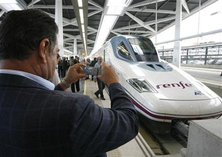 A man takes a picture of a high-speed AVE train, which has a top speed of between 300-350 kmh (186-217 mph), at the Joaquin Sorolla station after a 98-km (61-mile) test ride with passengers from Hoya de Roda to Valencia October 13, 2010. REUTERS/Heino Kalis