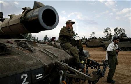 Israeli soldiers pray atop a tank at an Israeli Defence Forces (IDF) staging area by the central Gaza border November 22, 2012. A ceasefire between Israel and Gaza's Hamas rulers took hold on Thursday after eight days of conflict, although deep mistrust on both sides cast doubt on how long the Egyptian-sponsored deal can last. REUTERS/Yannis Behrakis (ISRAEL - Tags: CONFLICT CIVIL UNREST)