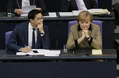 German Chancellor Angela Merkel and Leader of Germany's liberal Free Democrats FDP and Economy Minister Philipp Roesler attend a session of the German lower house of parliament Bundestag in Berlin November 21, 2012. REUTERS/Tobias Schwarz (GERMANY - Tags: POLITICS)