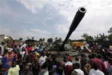 Los rebeldes en el este del Congo rechazaron el jueves los llamamientos para que abandonen la ciudad de Goma y amenazaron con presionar más hasta que el presidente Joseph Kabila acepte celebrar conversaciones de paz. En la imagen, la gente se congrega alrededor de un tanque abandonado por el ejército congolés en Ndosho, cerca de Goma, el 21 de noviembre de 2012. REUTERS/James Akena