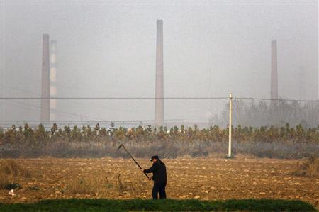 A farmer turns soil to plant crops with the chimneys from the huge state-owned lead smelter visible behind him in the town of Tianying, Anhui Province, November 19, 2012. REUTERS/David Gray