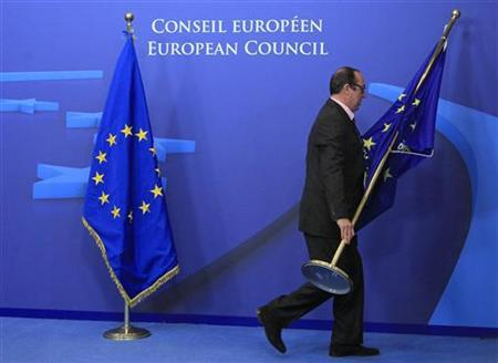 An employee at the EU council adjusts European Union flags at the entrance of the council headquarters for an European Union leaders summit discussing the European Union's long-term budget in Brussels November 22, 2012. REUTERS/Yves Herman
