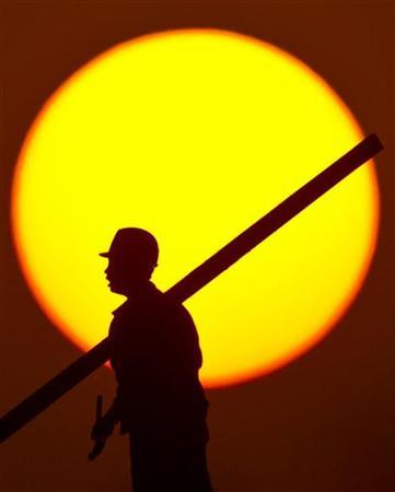 A construction worker installs scaffolding on the top of a building at sunset in Shanghai November 13, 2012. REUTER/Aly Song (CHINA - Tags: BUSINESS CONSTRUCTION POLITICS EMPLOYMENT)
