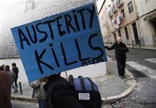 """Демонстрант держит плакат """"Экономия убивает"""" во время 24-часовой всеобщей забастовки в Лиссабоне 14 ноября 2012 года. Экономика еврозоны стоит на пороге слабейшего квартала с начала 2009 года, свидетельствуют данные бизнес-опросов, показавшие, что в ноябре 2012 года компании продолжали фиксировать сокращение заказов. REUTERS/Rafael Marchante"""